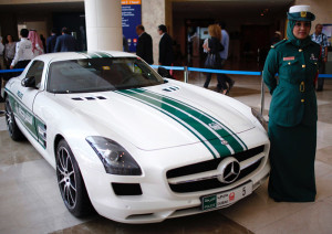 A police officer stands near a Mercedes car used by Dubai police, during the Arabian Travel Market exhibition in Dubai